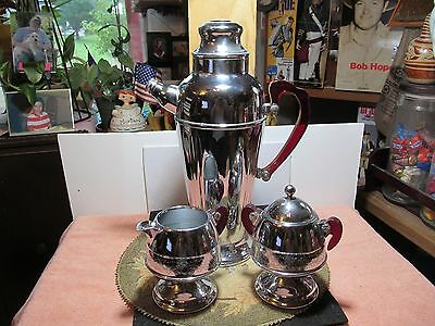 Vintage Deco style Chrome Plated carafe, creamer & sugar w/red bakelite handles.