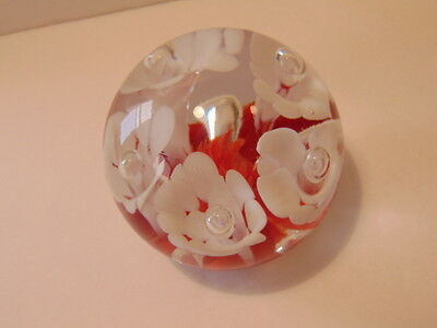Older round glass paperweight with white flowers by Joe St. Clair