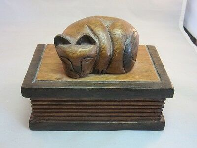 Hand carved wood box.Sleeping cat sitting on a book