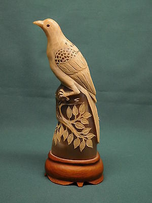 bird carved from horn wooden base