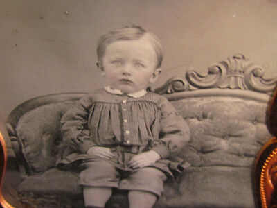 scared looking little boy sitting on a large victorian couch daguerreotype photo