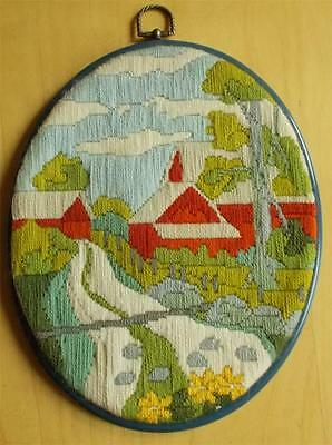 Swedish hand-embroidered oval picture, stream with red rural buildings, trees