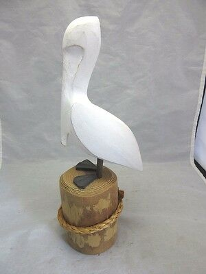 Hand carved wood figurine of a pelican on a dock post