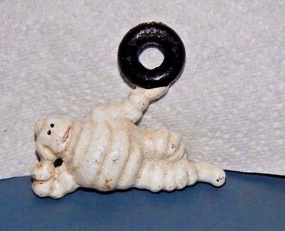 MICHELIN TIRE MAN FIGURINE Reclining Holding Tire Up CAST IRON Advertising Promo
