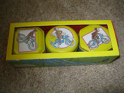 Curious George candles in decorative tins