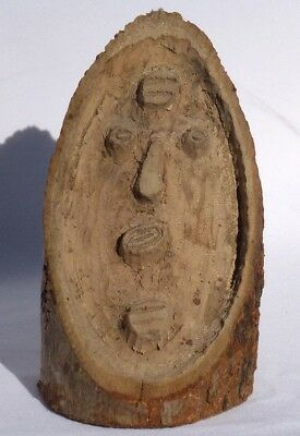 An odd relief carving of a face carved from the cut surface of an angled log.