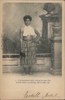 New Caledonia A Pacific Islander woman wearing a half-blouse and patterned saron
