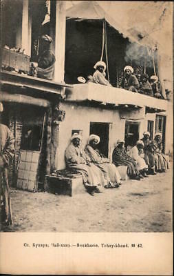 Uzbekistan Bukhara Men sitting and smoking along a two story building Postcard