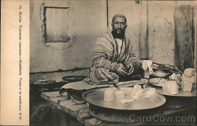 Uzbekistan Bukhara A seated man selling halvah in a shop stall Postcard
