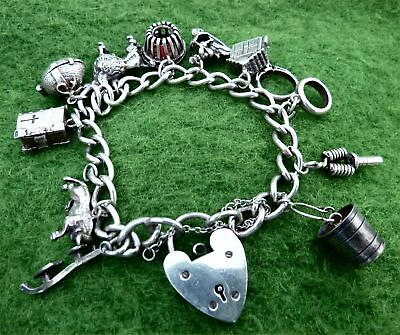 VINTAGE 1970s SILVER CHARM BRACELET WITH ELEVEN SMALL SILVER CHARMS - 1.60 oz