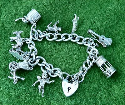 VINTAGE 1970s SILVER CHARM BRACELET WITH NINE SMALL SILVER CHARMS - 1.46 ozt