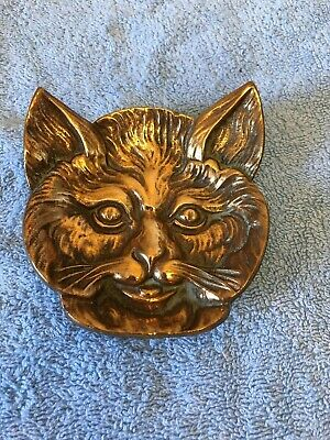 antique brass, cats face copper, number 27 on back, weight 1/2lb.