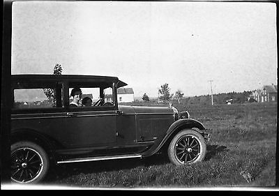 Old b/w photo negative young woman and girl in old antique car in field