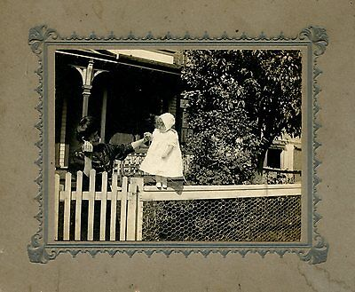 Old b/w cabinet photo young baby girl standing on fence rail with mom