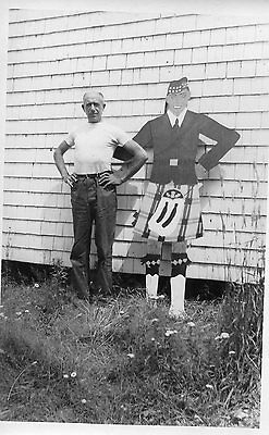 Old b/w photo man standing by wooden cut-out scottish kilt figure