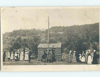 Pre-1920's rppc patriotic RAISING OF USA FLAG ON FLAGPOLE BY LOG CABIN HM0605