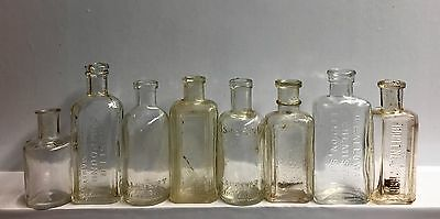 Eight Small Size Vintage Embossed Clear Glass Bottles.