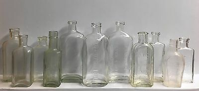 Eleven Small Size Vintage Embossed Clear Glass Bottles.