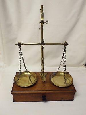 Antique brass beam scales on oak box with drawer.