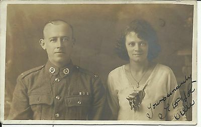 Unidentified soldier and his lady, signed, cannot make out the insignia