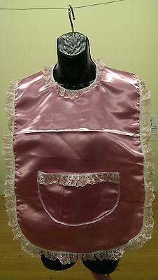 Waterproof backed satin bib with pocket and hook and loop fastening.