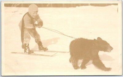 Vintage RPPC Real Photo Postcard Bear Cub Pulling Boy on Skis in Snow c1910s