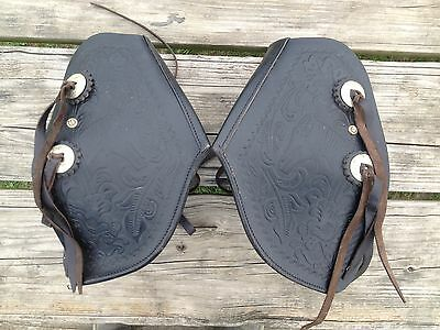 Pair used Western stirrups w/black leather tapaderos w/ tooled horse heads