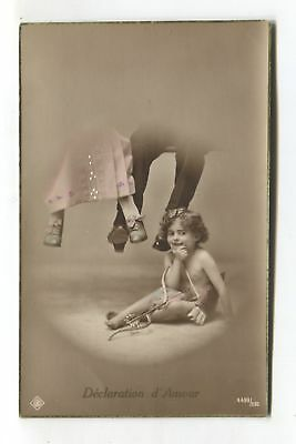Small child playing Cupid, hiding under table - old postcard