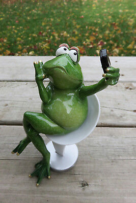 Frog Figurine Taking a Selfie Image Sitting on Chair Showing Off Frogs Ornament