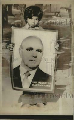 1974 Press Photo Boy shows off poster of Greek Premier Constantine Caramanlis
