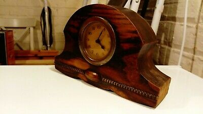 Very old mantel clock in wooden casing.