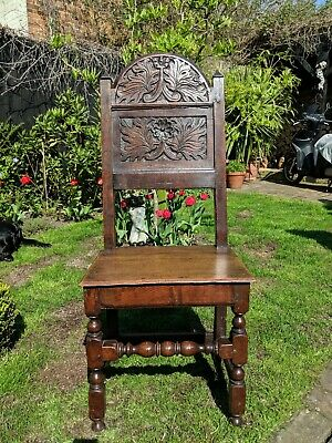 18th century oak chair with floral and leaf carving on turned legs.