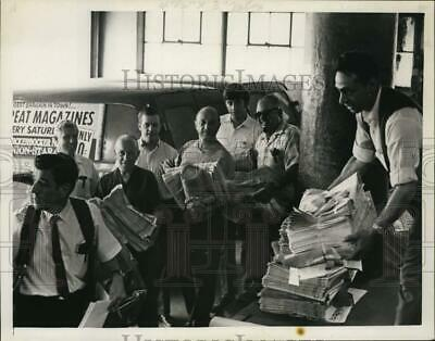 1969 Press Photo Julius Padula hands out bundles of newspapers to men lined up
