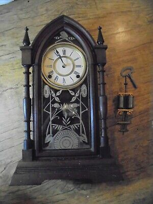 American Ansonia gothic style wooden cased mantle clock with key and pendulum.