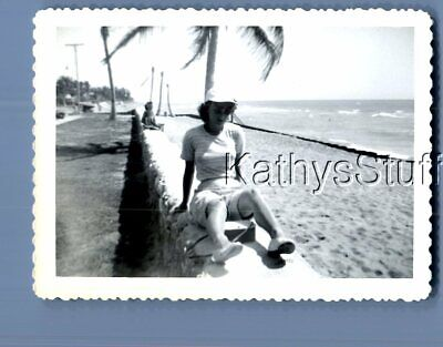 Found B&W Photo X_1068 Pretty Woman In Shorts And Hat Sitting On Wall