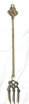 Traditional brass toasting fork with three wise monkeys on the handle