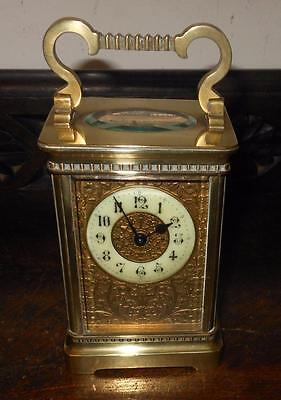 pretty brass cased mask dial carriage clock