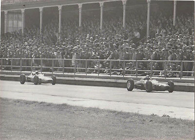 Two Singles Seater Cars Racing In Front Of Grandstand, Photograph.