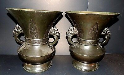 A Pair of Large Antique Chinese Bronze Urns with Decorative Dragon Handles.