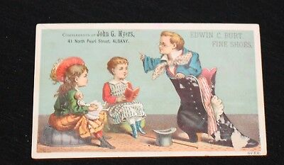 Boy Teacher, standing in Woman's Shoe, teaching Girls. Edwin Burt Shoes Adv Card