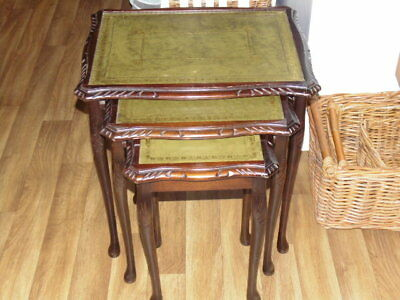 Dark wood carved and leather topped nest of tables