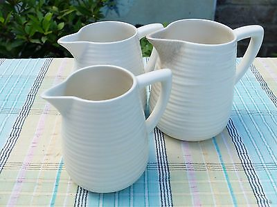 3 VINTAGE CLARICE CLIFF NEWPORT POTTERY OFF WHITE MILK JUGS - THREE SIZES banded