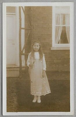 1920's era PC - Pretty young girl standing outside house holding wild flowers
