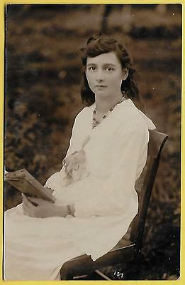 Edwardian/1920's Postcard - Very pretty young girl sitting and holding a book