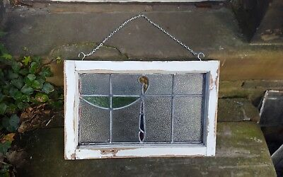 Old pieces of stained glass in wood frame with chain