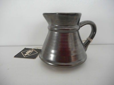 Prinknash small black jug with original label approx 6.5 cms high