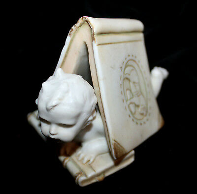 Antique Bisque Figurine of Child Peering out from Under an Open Book Crown & SW