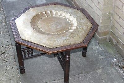 An antique brass topped Indian table with folding legs