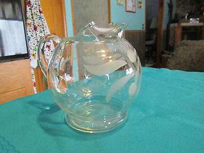 """Round glass pitcher etched design  6"""" tall and 7"""" wide with handle"""