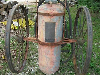 old ajax soda acid fire extingusher on two large iron wheels